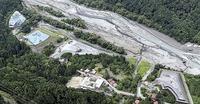 山梨県早川町塩島地区のリニア発生土置き場。大部分は仮置き。県道を挟んで手前の白い屋根は町立早川北小=7月下旬(本社ヘリ「ジェリコ1号」から)