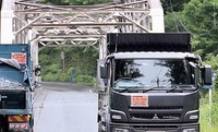 残土置き場の周辺を往来する「中央新幹線」の標識を掲げたダンプカー。橋の幅員が狭く、交互に通行していた=7月下旬、山梨県早川町
